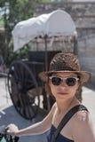 Die junge Frau in der Sonnenbrille und im Strohhut lizenzfreie stockfotos