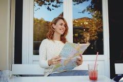 Die junge Frau des blonden Haares, die in der Kaffeestube und mit Lächeln sitzt, erwähnt die Plätze, die sie besichtigte lizenzfreie stockfotografie
