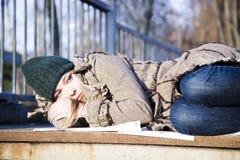 Die junge Frau, die auf Asphalt liegt Stockfotos