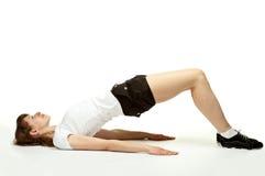 Die junge Frau, die auf dem Fußboden im Sport liegt, kleidet Lizenzfreies Stockbild