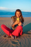 Die junge Frau, die auf dem Sand in der Wüste sitzt und betrachtet das Telefon Stockfotografie