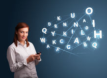 Die junge Frau, die auf smartphone mit High-Techem 3d schreibt, bezeichnet commi mit Buchstaben Stockfotografie