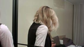 Die junge Frau, die Ausstattung vor einem Spiegel wählt und bitten eine Empfehlung um ihren Freund stock video