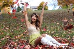 Die junge Frau, die in den Blättern sitzt, wirft sie in der Luft und lächelt Lizenzfreie Stockfotos