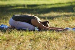 Die junge Frau, die in einem Haltung balasana mit den Armen sich entspannt, verlängerte Stockfotos