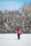 Die junge Frau, die in einen Schnee geht, setzte Forderung durch Stockfoto