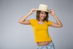 Die junge Frau, die gelben Hemdhut tragen und die kurze Jeanshose macht Gesicht Stockfotografie