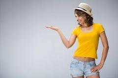 Die junge Frau, die gelben Hemdhut tragen und die kurze Jeanshose macht Gesicht Stockbild