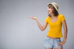 Die junge Frau, die gelben Hemdhut tragen und die kurze Jeanshose macht Gesicht Stockbilder
