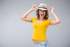 Die junge Frau, die gelben Hemdhut tragen und die kurze Jeanshose macht Gesicht Lizenzfreie Stockfotos