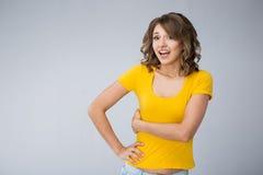Die junge Frau, die gelbes Hemd tragen und die kurze Jeanshose macht Gesichter Stockbilder