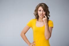 Die junge Frau, die gelbes Hemd tragen und die kurze Jeanshose macht Gesichter Lizenzfreies Stockbild