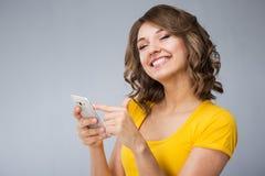 Die junge Frau, die gelbes Hemd tragen und die kurze Jeanshose spricht mit Telefon Stockbilder