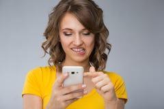 Die junge Frau, die gelbes Hemd tragen und die kurze Jeanshose spricht mit Telefon Stockfotos