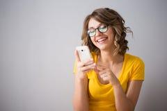 Die junge Frau, die gelbes Hemd tragen und die kurze Jeanshose spricht mit Telefon Lizenzfreie Stockfotos