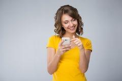 Die junge Frau, die gelbes Hemd tragen und die kurze Jeanshose spricht mit Telefon Stockbild