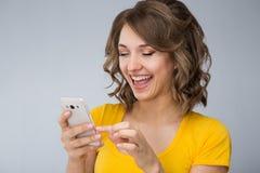 Die junge Frau, die gelbes Hemd tragen und die kurze Jeanshose spricht mit Telefon Lizenzfreie Stockfotografie