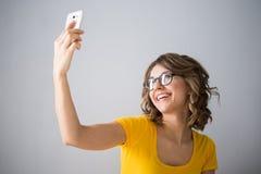 Die junge Frau, die gelbes Hemd tragen und die kurze Jeanshose spricht mit Telefon Stockfoto