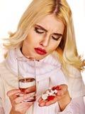 Die junge Frau, die Grippe hat, nimmt Pillen ein. Lizenzfreie Stockbilder