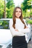Die junge Frau, die mit den gekreuzten Armen steht, nähern sich Auto stockfotografie