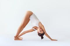 Die junge Frau, die Yoga asana tut, rotierte abwärtsgerichtetes Hund-isolat Stockbild