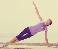 Die junge Frau, die Yoga tut, wirft das Sitzen auf sonnigem Strand auf Stockbilder