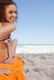Die junge Frau drehend ihre gehen zurück beim Sitzen auf dem Strand voran Lizenzfreie Stockbilder