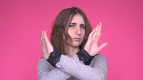Die junge Frau, die einen Halt zeigt, bewaffnet gekreuzt beim Betrachten der Kamera über rosa Hintergrund stock video footage