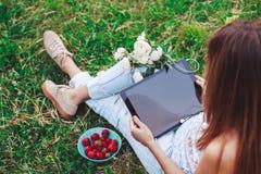 Die junge Frau, die einen Tabletten-PC sitzt im Sommergras mit Blumenstrauß von Pfingstrosen verwendet, blüht Lizenzfreies Stockbild