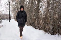 Die junge Frau, die entlang einen Schnee geht, bedeckte Fußweg Lizenzfreies Stockbild