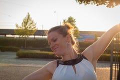 Die junge Frau freut sich Morgensonne an einer Bushaltestelle Lizenzfreies Stockbild