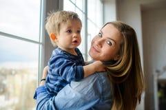 Die junge Frau hält auf Händen des kleinen Sohns Stockbild