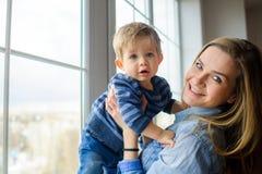 Die junge Frau hält auf Händen des kleinen Sohns Stockbilder