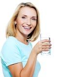 Die junge Frau hält ein Glas mit Wasser an Stockfotografie