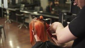 Die junge Frau, die ihr Haar erhält, kleidete im Friseursalon an Stilist-Friseur bei der Arbeit Bürstendes Haar des Mannfriseurs  stock video footage