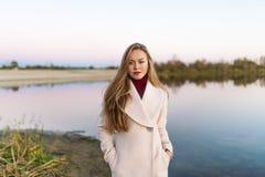 Die junge Frau, die im Herbstpark aufwirft, steht sie den See bereit stockbild