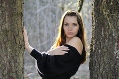 Die junge Frau im Park zwischen Bäumen Lizenzfreie Stockfotos