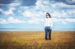 Die junge Frau, die inmitten eines orange Rasens lächelt, betrachtet sie die Kamera, so sorglos Hügel bedeckte trockenes Gras Bas Stockfotos
