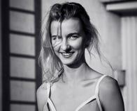 Die junge Frau kleidete im Badeanzug lächelnd an der Kamera an Tag, im Freien Stockfoto