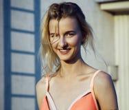 Die junge Frau kleidete im korallenroten Badeanzug lächelnd an der Kamera an Tag, im Freien Lizenzfreies Stockbild