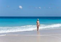 Die junge Frau kommt zu einem sandigen Strand ihrer Wellen des Meeres Lizenzfreies Stockbild
