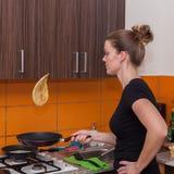 Die junge Frau macht Pfannkuchen Stockfotos