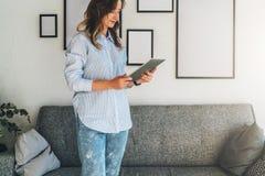 Die junge Frau mit dem blonden Haar steht im Wohnzimmer nahe bei Sofa und benutzt Tablet-Computer, blogging und plaudert Lizenzfreie Stockfotos
