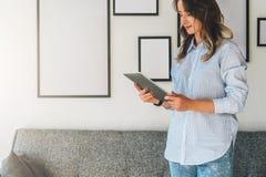 Die junge Frau mit dem blonden Haar steht im Wohnzimmer nahe bei Sofa und benutzt Tablet-Computer, blogging und plaudert Lizenzfreies Stockfoto