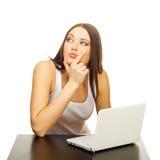 Die junge Frau mit dem Laptop hinter einer Tabelle Lizenzfreie Stockfotografie