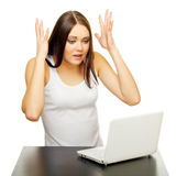 Die junge Frau mit dem Laptop hinter einer Tabelle Stockfotografie