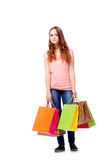 Die junge Frau mit den Einkaufstaschen lokalisiert auf Weiß Stockfotografie