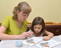 Die junge Frau mit der kleinen Tochterfarbe mit Farben eine Vogelzufuhr Stockbilder