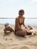 Die junge Frau mit ihrem Sohn und Welpen auf dem Strand Lizenzfreies Stockfoto
