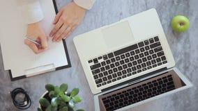 Die junge Frau, die mit Laptop arbeitet und auf die Papieridee, bei Tisch sitzend schreibt, whis grünen Apfel stock video footage